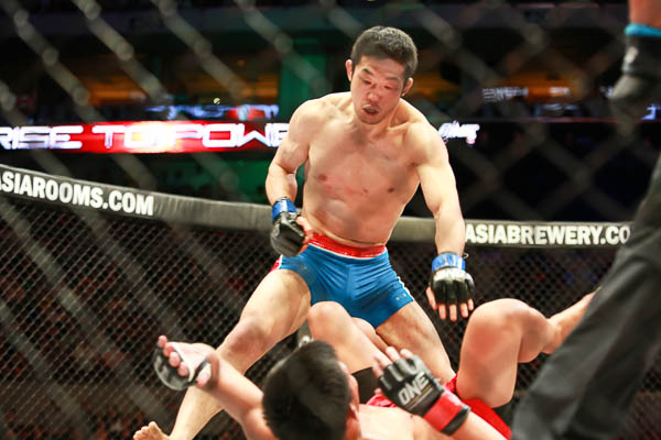 Koji Oishi standing over Honorio Banario to cement one of the most dominant boogeyman rivalries.